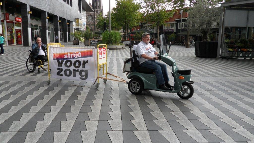 Cees en Frans met bed achter scootmobiel en in rolstoel