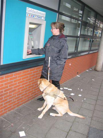 Kim met geleidehond bij pinautomaat