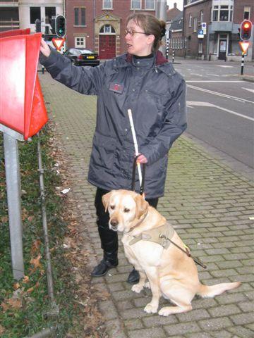Kim met geleidehond bij de brievenbus