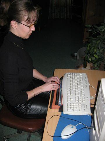 Vrouw achter aangepaste computer met brailleleesregel