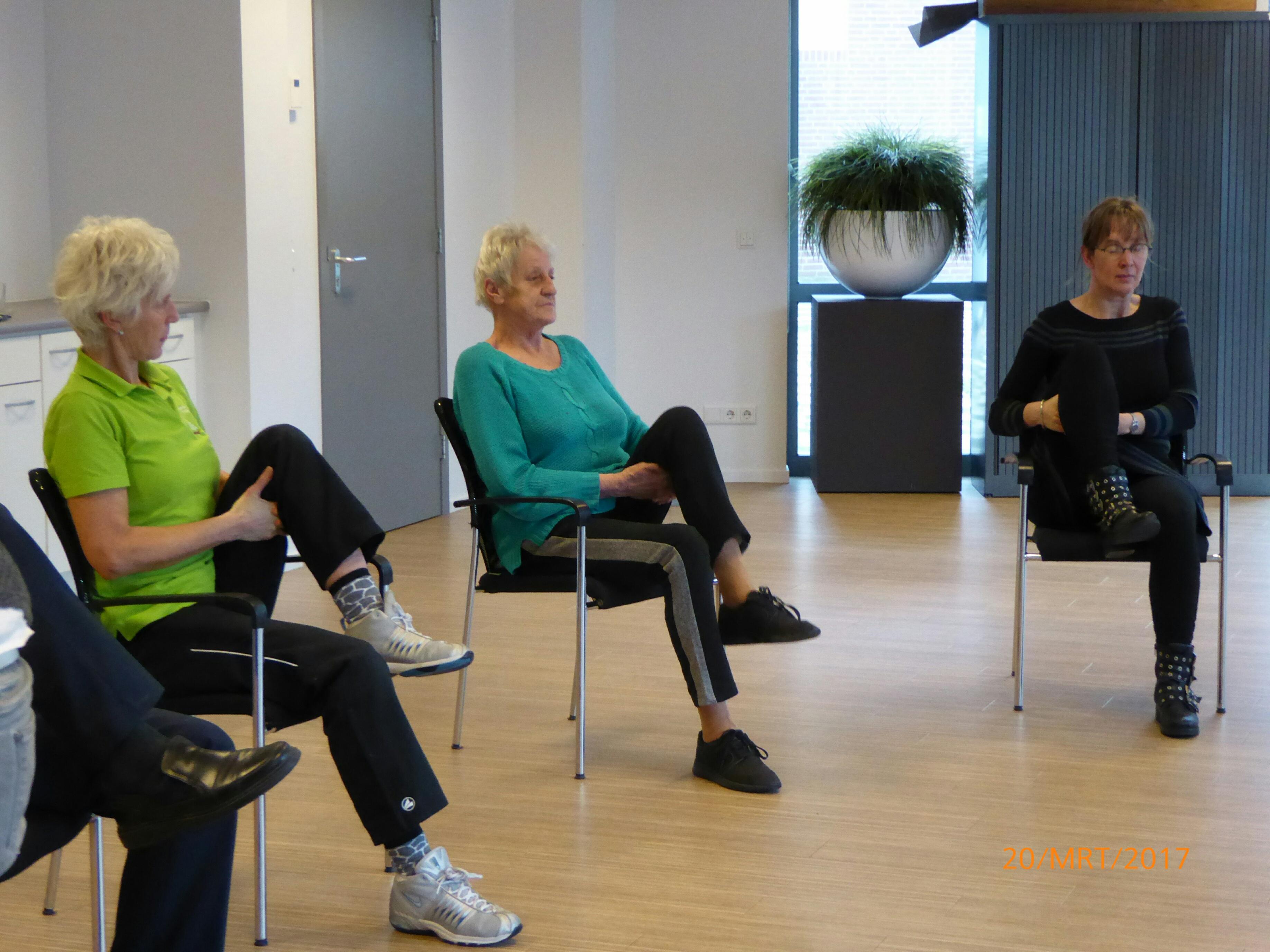 De groep doet oefeningen zittend op een stoel